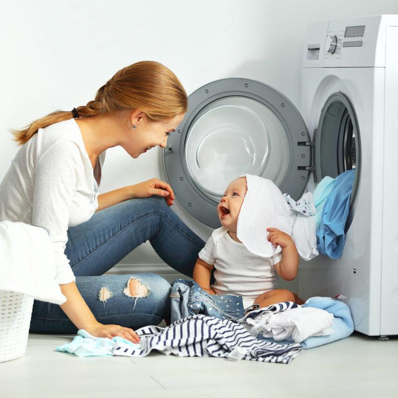 Cross Sector expertise. Mother and baby next to washing machine - BlueThink Technology, Engineering, Industrial, Product, Design and Mechanical Consultants and assisting with Home appliance mechanical engineering