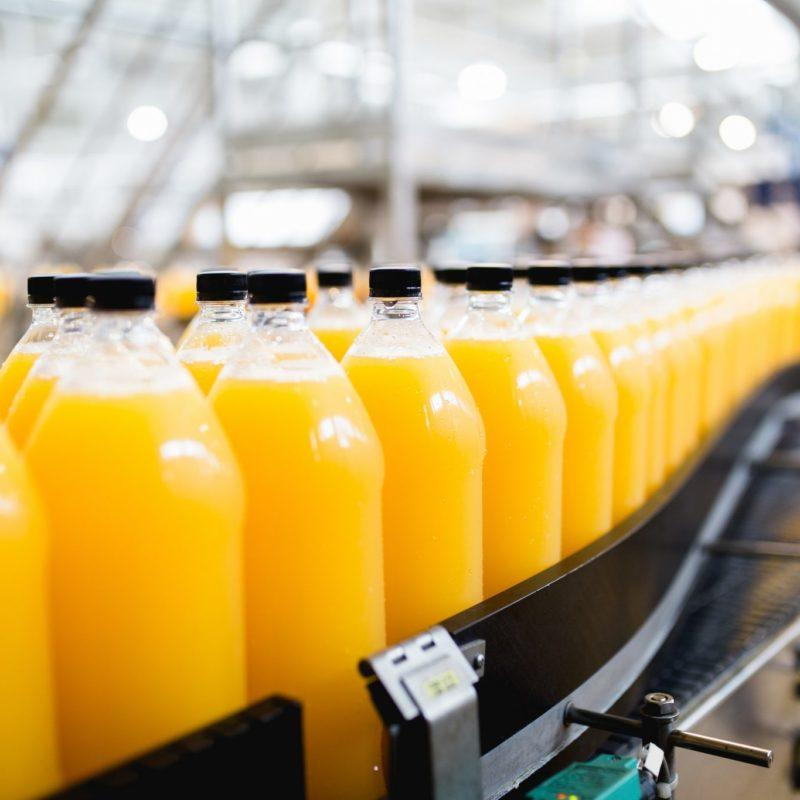 food and beverage manufacturing Orange cartons on conveyor belt - BlueThink Technology, Engineering, Industrial, Product, Design and Mechanical Consultants and assisting with food and beverage manufacturing